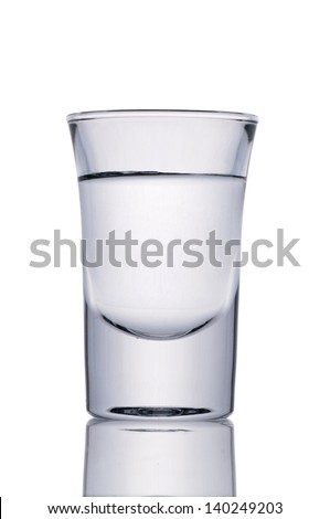 Small shot glass filled with alcohol isolated on white - stock photo