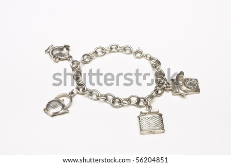 Small silver charm bracelet with 4 charms isolated against white background. - stock photo