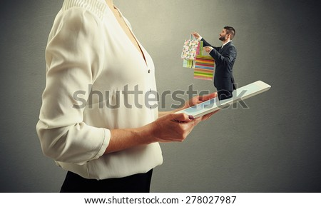 small smiley man got out of the tablet pc and offering shopping paper bags to the big woman in formal wear over dark grey background - stock photo