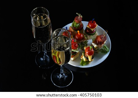 Small snacks canape with cherry tomatoes, cheese, sausages and vegetables on bread on skewers on white plate with two glasses of champagne against rustic wooden background, horizontal overhead view - stock photo