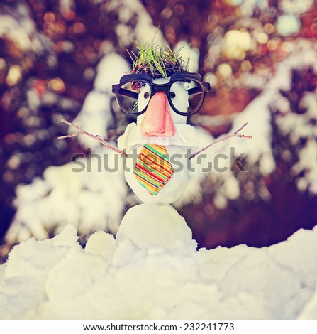 small snowman in snow with a hipster tie and glasses on toned with a retro vintage instagram filter  - stock photo