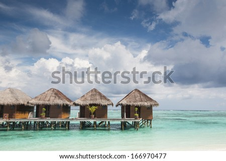 Small SPA wooden houses on sea, located in Maldives region - stock photo