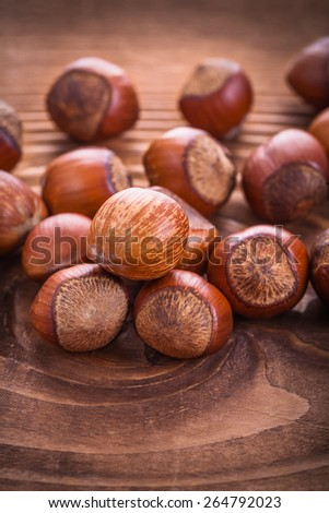 small stack of hazelnuts on vintage wooden board food and drink concept  - stock photo