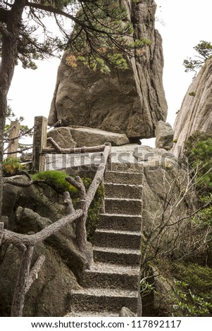 Small staircase in China's Yellow Mountain Trails with large rock and sky in background - stock photo
