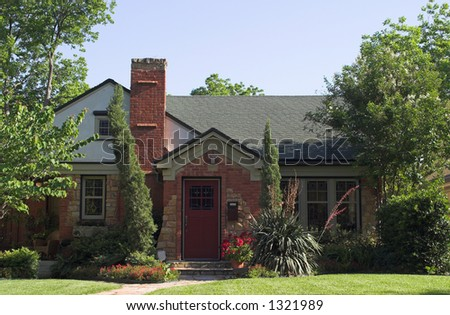 small stone and brick cottage with extensive, colorful landscaping - stock photo