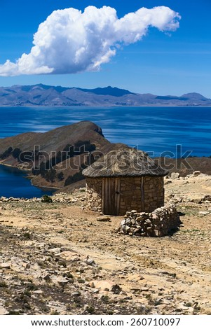 Small stone hut with thatched roof on Isla del Sol (Island of the Sun) in Lake Titicaca, Bolivia. The island is a popular tourist destination.  - stock photo
