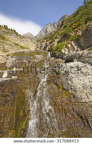 Small Stream Running Down the Slope of the Garden Wall along the Highline Trail in Glacier National Park - stock photo