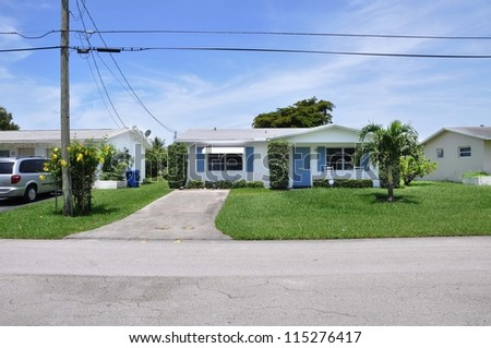 Small suburban cottage style home driveway telephone pole electrical lines sunny blue sky day - stock photo