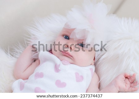 Small  sweet baby girl with white flower headband is lying on the fluffy blanket - stock photo