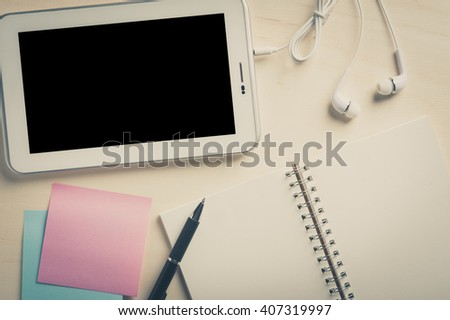 Small tablet pc with blank area on touchscreen, in ear headset, notebook, sticky paper, and pen on wood table with vintage filter effect - stock photo