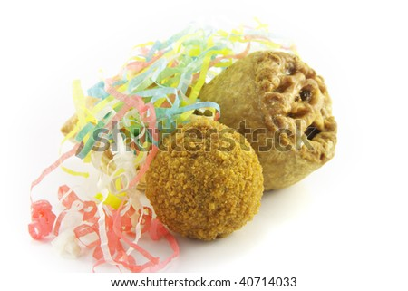 Small tasty pork pie with small round scotch egg and streamers on a reflective white background - stock photo