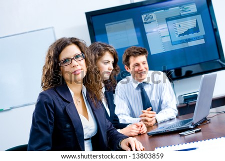 Small team of young businesspeople working together at meeting room at office. Huge plasma TV screen in background. - stock photo