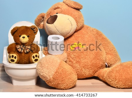 Small teddy bear sitting on the potty and playing with toilet paper, father bear teaching his cute kid how to pee and poo - stock photo