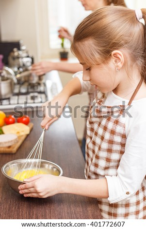 Small teenage girl whisks eggs in the mixing bowl at the kitchen. Mother and daughter cooking breakfast together - stock photo