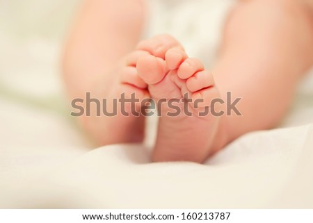 Small tiny baby feet on the bed,  ready for your text or symbols - stock photo