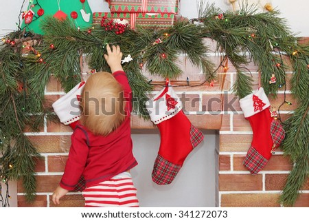 Small toddler boy reaching for a gift on the Christmas decorated fireplace, back view, focus on arm, winter holiday family concept  - stock photo