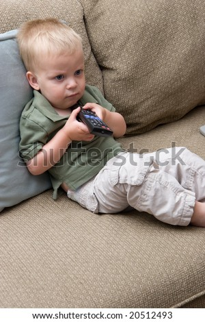 small toddler who is not happy with the choices on the television - stock photo