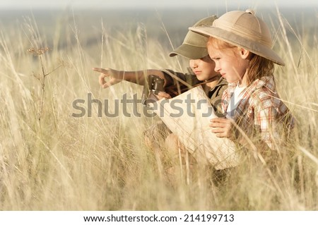 Small tourists looking into the distance through the thick grass steppe in summer sunny day  - stock photo