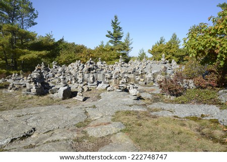 small towers of stones on top of Mount Battie in Camden, Maine.  There are many trees and foliage with a bright blue sky overhead. - stock photo