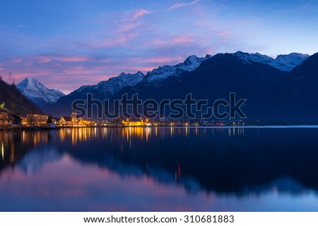 Small town in Swiss Alps. Night sky and clouds sunset painted in red.  Lanterns and lights reflected in water of lake. - stock photo
