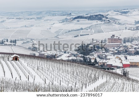 Small town of Barolo and vineyards on hills covered with snow in Piedmont, Northern Italy. - stock photo