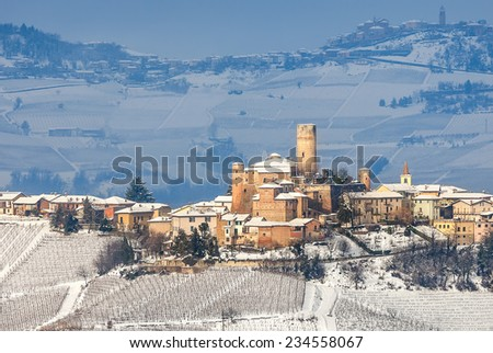 Small town of Castiglione Falletto and vineyards on hills covered with snow in Piedmont, Northern Italy. - stock photo