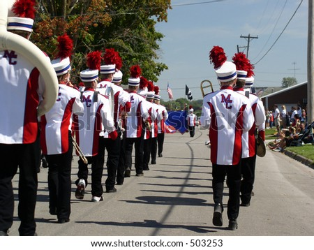 Small town school marching band has a big part in local parades. Colorful uniforms and bright music add to the festive occasion. - stock photo