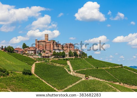 Small town with medieval castle among green vineyards under blue sky in Piedmont, Northern Italy. - stock photo