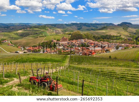 Small tractor among green vineyards and small town of Barolo on background in Piedmont, Northern Italy. - stock photo