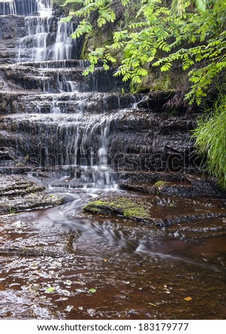 Small trickling waterfall in Yorkshire woodland - stock photo