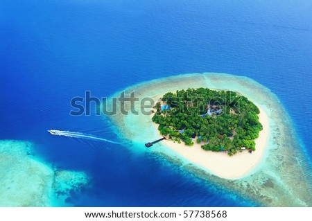Small tropical island in the ocean, Maldives. Shot was taken from seaplane. - stock photo