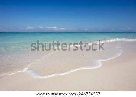 Small tropical waves lap onto a white sand beach on a sunny day. - stock photo