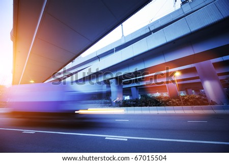 Small truck speeding under industrial bridges. Long exposure, burred motion. - stock photo