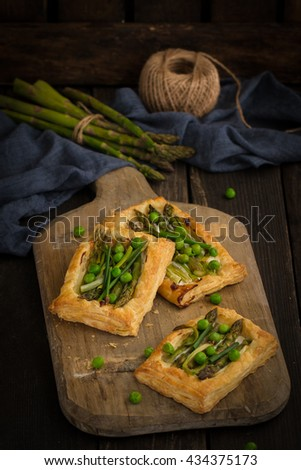 Small vegetable tarts with puff pastry , green peas and  asparagus . Delicious vegetarian appetizers . - stock photo