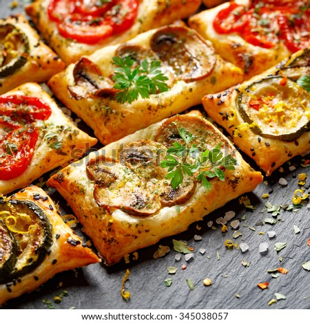 Small vegetable tarts with puff pastry, tomato, mushrooms and zucchini. Delicious vegetarian appetizers - stock photo
