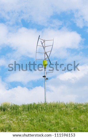 small vertical axis wind turbine on a green hill - stock photo
