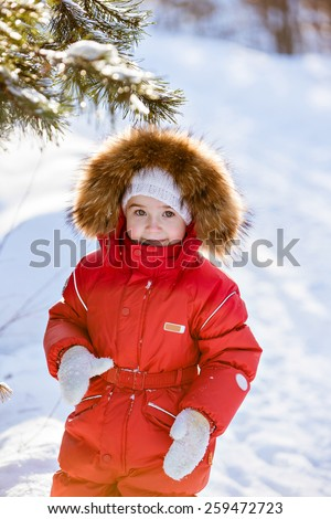 Small very cute girl in a red suit with fur hood costs about trees in winter forest background - stock photo