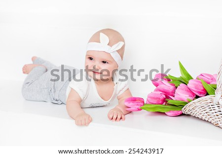 Small very cute wide-eyed smiling baby girl lying on her tummy on a white background in the Studio, next to the tulips - stock photo