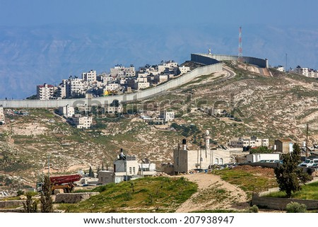 Small village and palestinian town on the hill behind separation wall on the West Bank in Israel. - stock photo