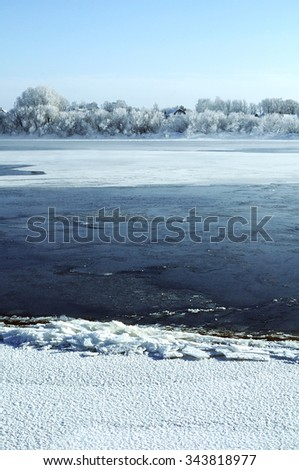 Small village at the bank of the river in sunny winter day - winter rural landscape  - stock photo