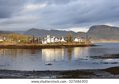 Small village on the shores of Loch Carron and a small island off the west coast village of Plockton, in Scotland, is home to a small number of trees and the occasional seal. - stock photo