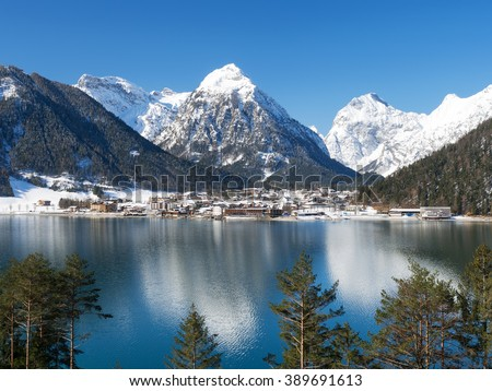 Small village Pertisau at Lake Achensee with snow-covered mountains in the background, Tyrol, Austria - stock photo