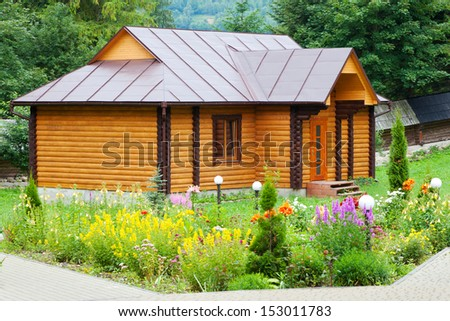 small village wooden house with flower bed - stock photo