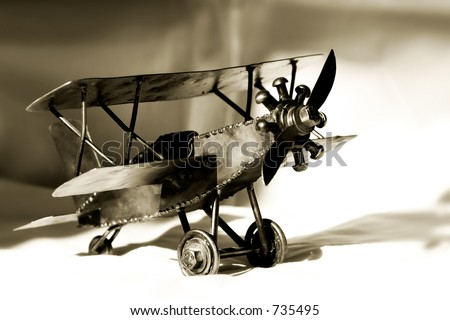 Small vintage metal barnstormer Bi-Plane in sepia tone - represents aviation and travel. - stock photo