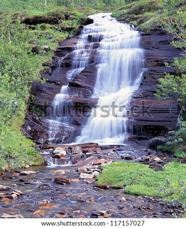 Small waterfall and stream in the hill - stock photo