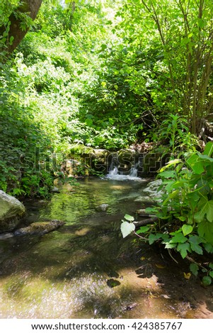 Small waterfall in a forest stream Kziv in the north of Israel - stock photo