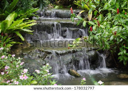 small waterfall in the park Asian with flowers and plants - stock photo