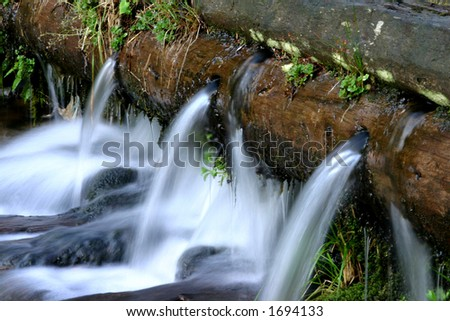 Small waterfall of a dam in Retezat mountains - Romania - stock photo