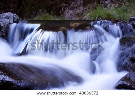 Small waterfall on coastal stream - stock photo