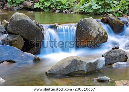 small waterfall on mountain stream - stock photo